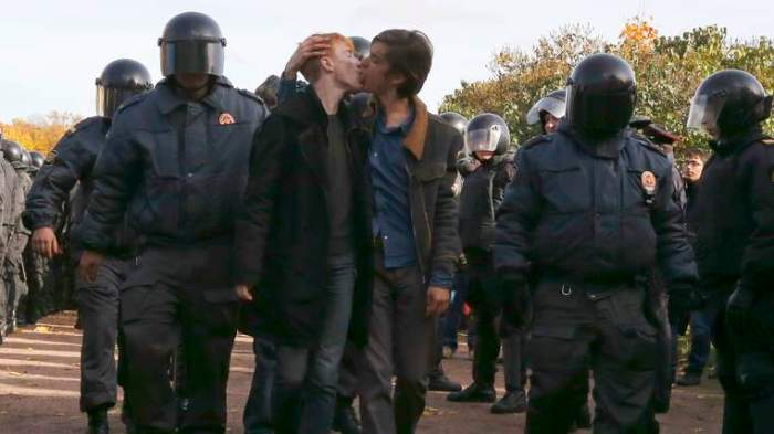 Gay rights activists kiss as they are detained by police officers during a gay rights protest in St. Petersburg